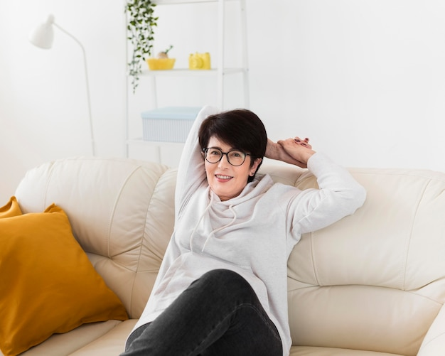 Vorderansicht der smileyfrau, die zu hause auf sofa entspannt