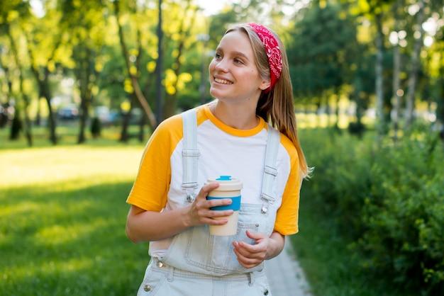 Vorderansicht der smileyfrau draußen mit tasse