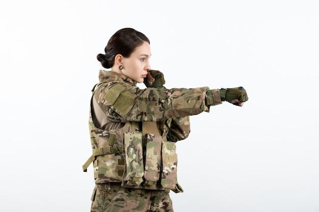 Vorderansicht der soldatin in tarnung, die bereit ist, gegen die weiße wand zu kämpfen