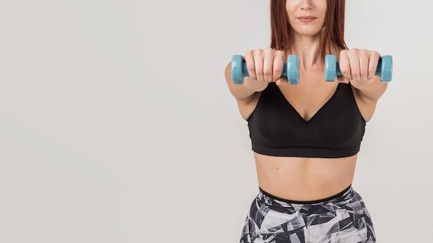 Vorderansicht der sportlichen frau, die mit gewichten ausübt