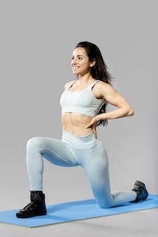 Vorderansicht der sportlichen frau, die übungen macht