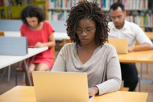 Vorderansicht der starken frau arbeitend mit laptop an der bibliothek