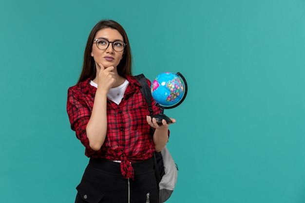 Vorderansicht der studentin, die rucksack hält, der kleinen globus auf hellblauer wand hält