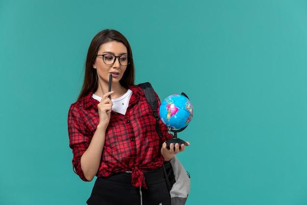 Vorderansicht der studentin, die rucksack hält, der kleinen globus und stift auf hellblauer wand hält