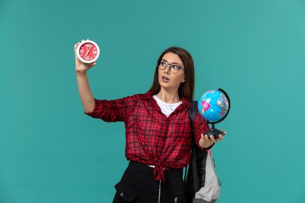 Vorderansicht der studentin, die rucksack hält, der kleinen globus und uhren auf hellblauer wand hält