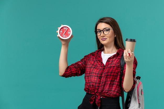 Vorderansicht der studentin, die rucksack hält, der uhren und kaffee an der blauen wand hält