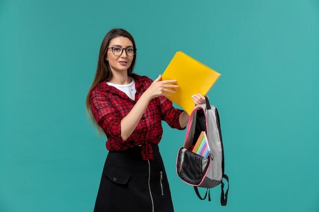 Vorderansicht der studentin, die rucksack und akten an der hellblauen wand hält