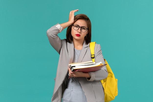 Vorderansicht der studentin im gelben rucksack der grauen jacke, der bücher an der hellblauen wand hält