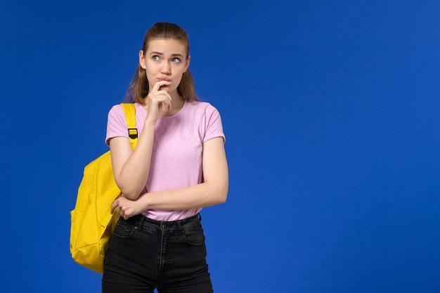 Vorderansicht der studentin im rosa t-shirt mit gelbem rucksack, der an hellblaue wand denkt