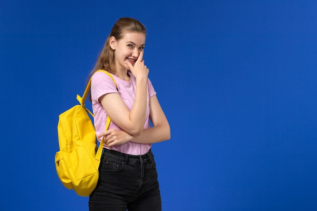 Vorderansicht der studentin im rosa t-shirt mit gelbem rucksack, der auf blauer wand lacht