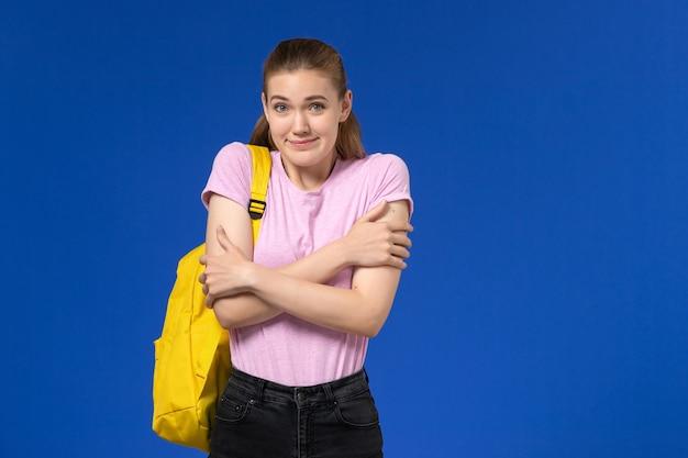Vorderansicht der studentin im rosa t-shirt mit gelbem rucksack, der gerade auf der blauen wand steht