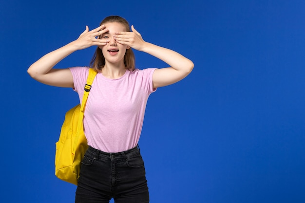Vorderansicht der studentin im rosa t-shirt mit gelbem rucksack, der ihre augen auf hellblauer wand schließt