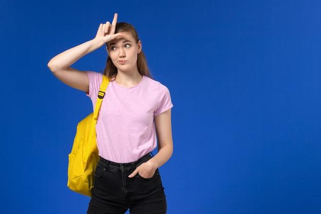 Vorderansicht der studentin im rosa t-shirt mit gelbem rucksack
