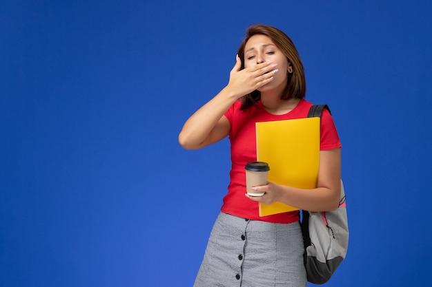 Vorderansicht der studentin im roten hemd mit dem rucksack, der gelbe dateien und kaffee gähnt, die auf blauer wand gähnen