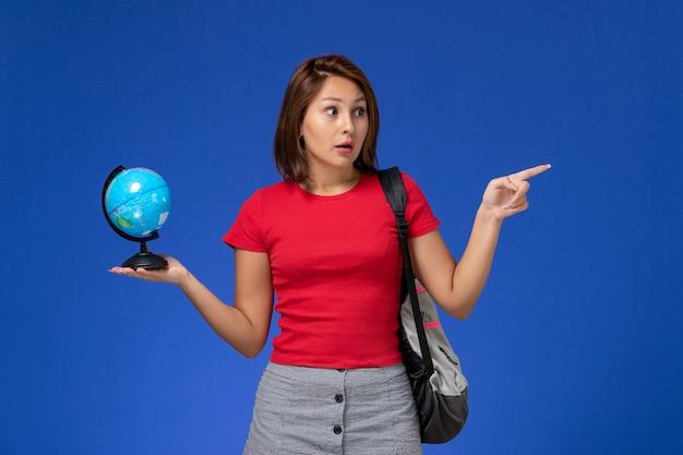 Vorderansicht der studentin im roten hemd mit dem rucksack, der kleinen globus auf hellblauer wand hält