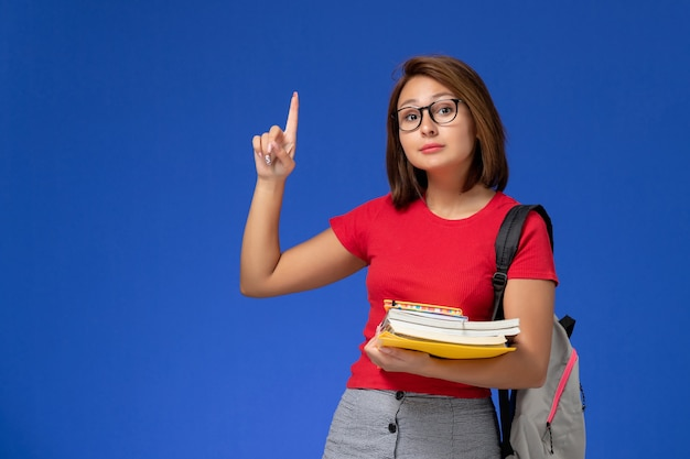 Vorderansicht der studentin im roten hemd mit rucksack, der bücher und akten an der hellblauen wand hält
