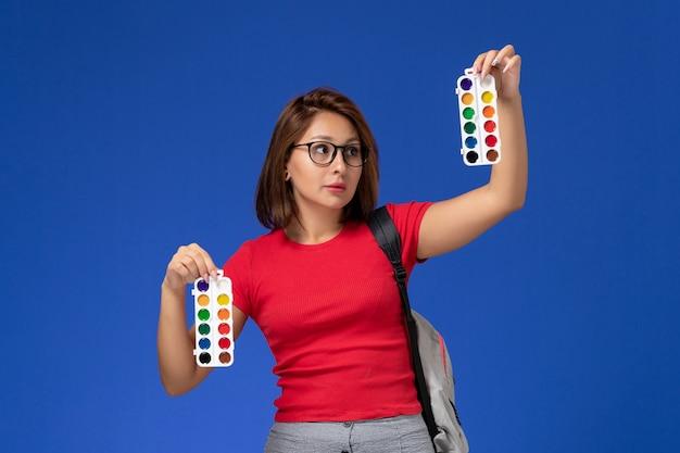 Vorderansicht der studentin im roten hemd mit rucksack, der farben für das zeichnen auf der blauen wand hält