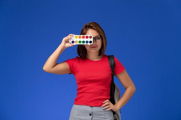 Vorderansicht der studentin im roten hemd mit rucksack, der farben zum zeichnen hält