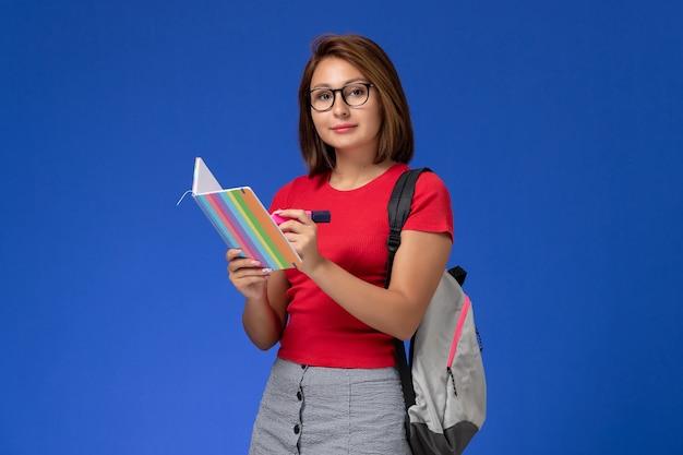 Vorderansicht der studentin im roten hemd mit rucksack, der filzstifte und heft auf blauer wand hält