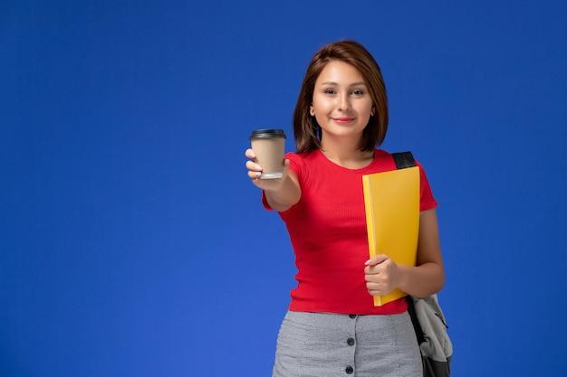 Vorderansicht der studentin im roten hemd mit rucksack, der gelbe dateien und kaffee auf blauer wand hält
