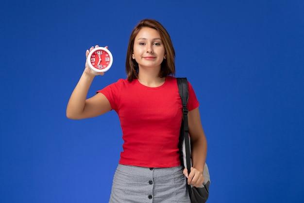 Vorderansicht der studentin im roten hemd mit rucksack, der uhren an der blauen wand hält