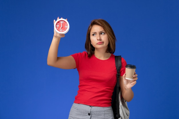 Vorderansicht der studentin im roten hemd mit rucksack, der uhren und kaffee an der blauen wand hält