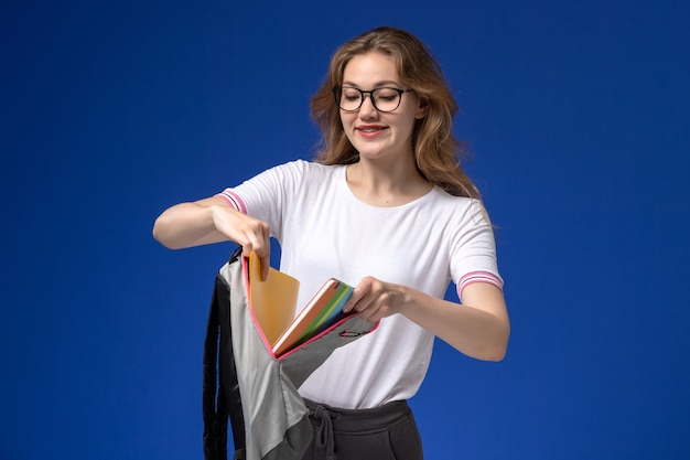 Vorderansicht der studentin im weißen hemd, das rucksack und gelbe dateien an der blauen wand hält