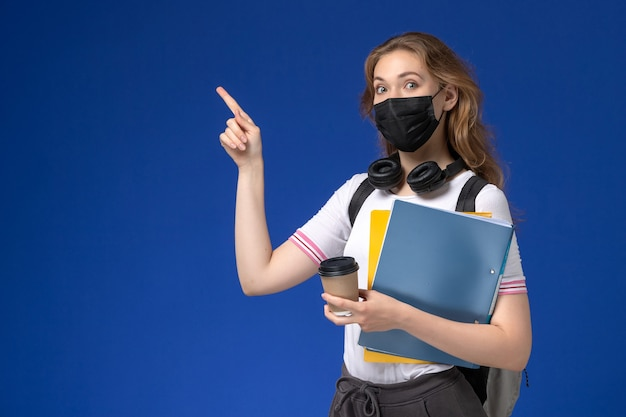 Vorderansicht der studentin im weißen hemd, das schwarze sterile rucksackmaske hält, die kaffee und dateien an der blauen wand hält