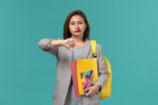 Vorderansicht der studentin in der grauen jacke, die gelben rucksack hält, der dateien und heft hält, das unähnliches zeichen auf blauer wand zeigt