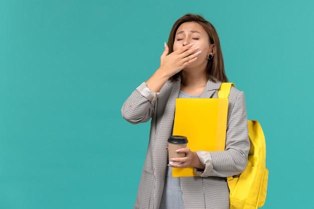 Vorderansicht der studentin in der grauen jacke, die ihren gelben rucksack hält, der dateien und kaffee hält, die auf hellblauer wand gähnen