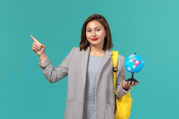 Vorderansicht der studentin in der grauen jacke, die ihren gelben rucksack hält, der kleinen globus auf hellblauer wand hält