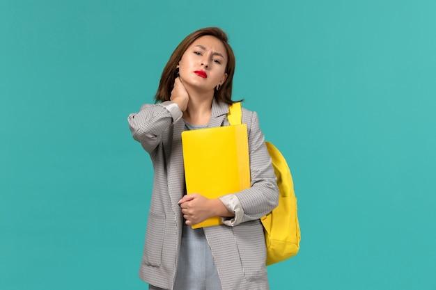 Vorderansicht der studentin in der grauen jacke, die ihren gelben rucksack trägt und akten an der hellblauen wand hält