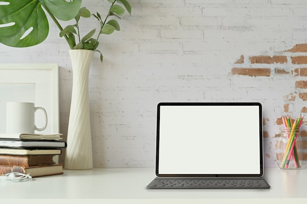 Vorderansicht der tablette mit intelligenter tastatur auf dachbodenarbeitsplatztabelle.