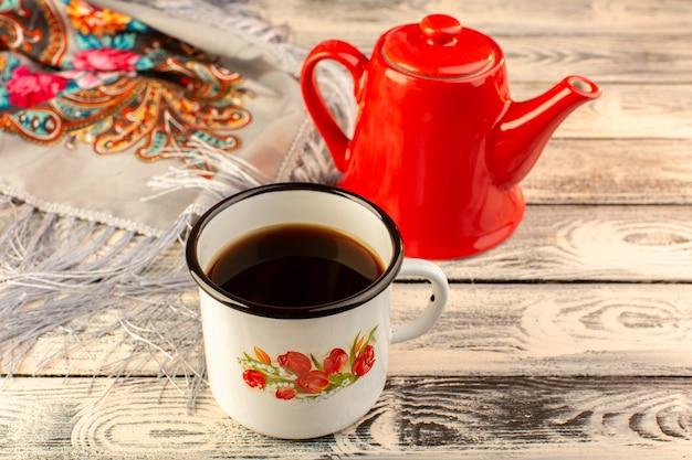 Vorderansicht der tasse kaffee mit rotem kessel auf dem hölzernen schreibtisch