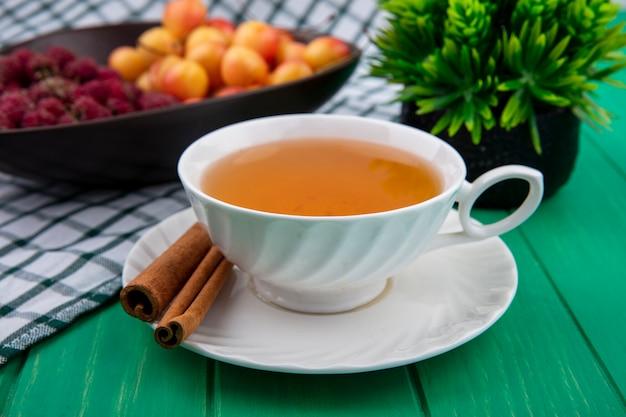 Vorderansicht der tasse tee mit zimthimbeeren und weißen kirschen auf einer grünen oberfläche