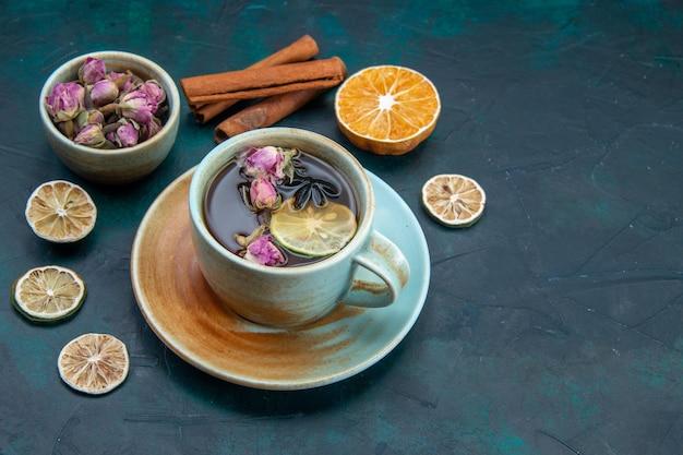 Vorderansicht der tasse tee mit zitrone und blume auf dunklem schreibtisch