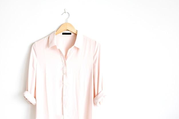 Vorderansicht der trendigen rosa weiblichen bluse der schönheit auf kleiderbügel nahe weißem hintergrund. mode-konzept.