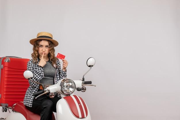 Vorderansicht der trüben jungen frau auf moped, das karte auf grauer wand hält