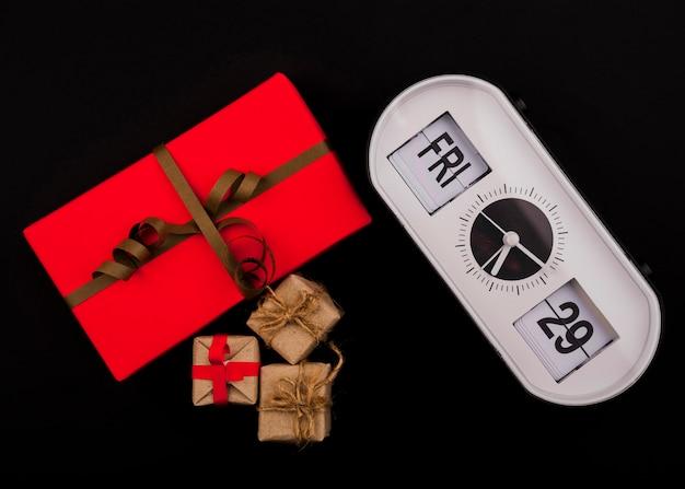 Vorderansicht der uhr und des geschenkes auf schwarzem hintergrund