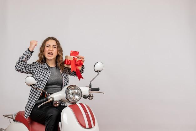 Vorderansicht der verärgerten jungen frau auf moped, das geschenk auf grauer wand hält