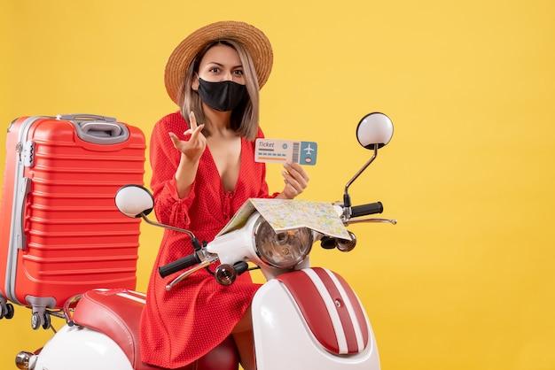 Vorderansicht der verwirrten jungen dame mit schwarzer maske auf moped-haltekarte