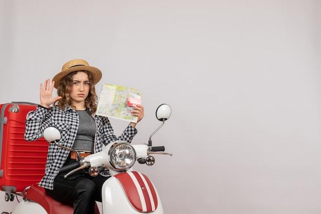 Vorderansicht der verwirrten jungen frau auf moped, die karte und karte auf grauer wand hält