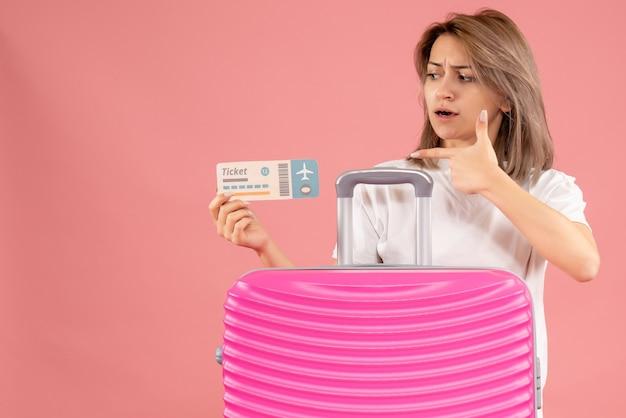 Vorderansicht der verwirrten jungen frau, die auf ticket hinter rosa koffer zeigt