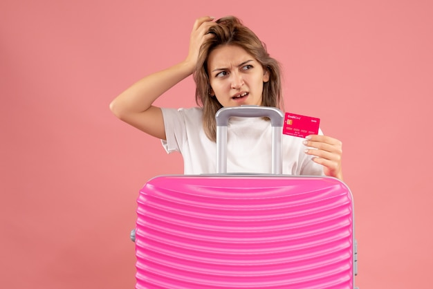 Vorderansicht der verwirrten jungen frau, die karte hinter rosa koffer hält