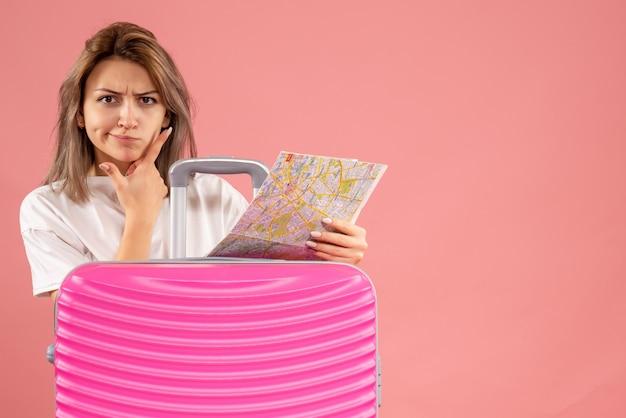 Vorderansicht der verwirrten jungen frau mit rosa koffer, die karte hält