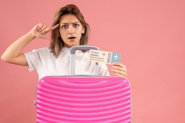 Vorderansicht der verwirrten jungen frau mit rosa koffer, die ticket hält