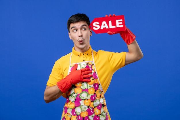 Vorderansicht der verwunderten männlichen haushälterin in gelbem t-pullover mit verkaufsschild an blauer wand