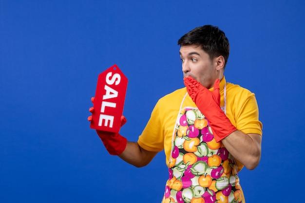 Vorderansicht der verwunderten männlichen haushälterin in gelbem t-shirt, die ein verkaufsschild hält und die hand auf den mund auf die blaue wand legt