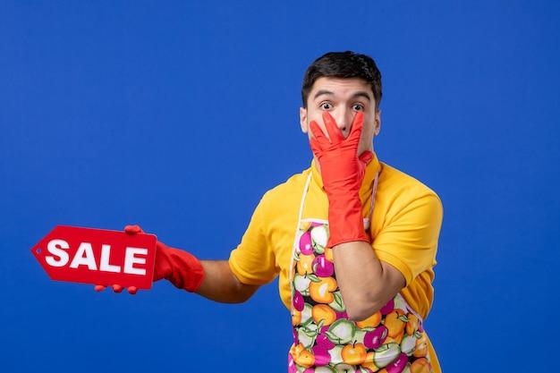 Vorderansicht der verwunderten männlichen haushälterin in gelbem t-shirt, die ein verkaufsschild hält und die hand auf sein gesicht auf die blaue wand legt