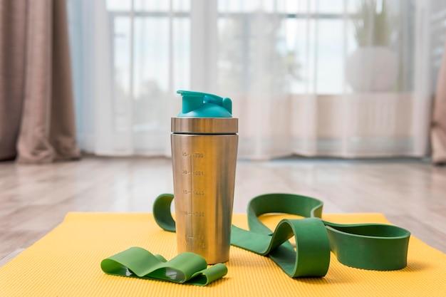 Vorderansicht der wasserflasche und des gummibands für das training zu hause